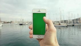 Green Screen Mobile Phone With Yachts Sunny Day. Man Hand Using Green Screen Mobile Phone Against in Front of the Pier with Yachts in the Sunny Day stock video footage