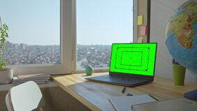 Green screen mock up laptop on wooden desk.