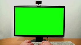 Green screen monitor and keyboard. Close-up of man's hands typing on a keyboard and a green screen stock video footage