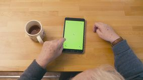 Green screen. Old woman scrolling the tablet stock video