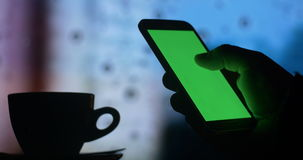 Green screen phone drinking coffee tea city night. Dark silhouette close up of a mans hand using a tablet computer pc to check internet stock market exchange and stock video footage