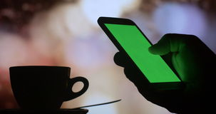Green screen phone drinking coffee tea city night. Dark silhouette close up of a mans hand using a tablet computer pc to check internet stock market exchange and stock footage