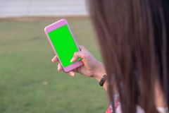 Green screen phone in the hands of the girl. royalty free stock photos
