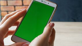 Green screen smartphone. Chroma Key on a white smartphone, female hands hold mobile phone in cafe. Green screen smartphone. Chroma Key on a white smartphone stock video footage