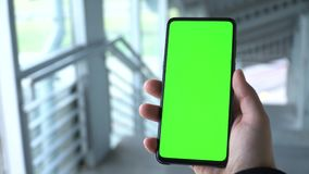 Green screen smartphone. A man`s hand holds a phone. Scrolling on the green screen of the phone. Smartphone footage. stock video