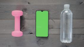Green screen - A Smartphone, water bottle and a dumbbell on a table stock video footage
