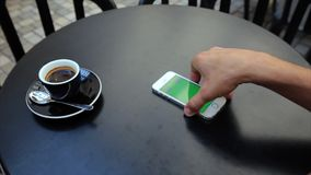Green screen to receive a call on the phone in. A man sits at a table in a cafe with a phone in white, green screen, vertical screen position. Action: on a table stock video footage