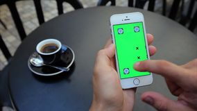 Green screen to scroll through web pages. A man sits at a table in a cafe with a phone in white, green screen, vertical screen position. Actions: scroll pages stock video