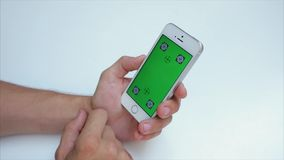 Green screen to scroll through web pages. A man sits at a table in a cafe with white phone in white, green screen, vertical screen location. Actions: Flip the stock video