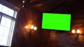 Green Screen TV on a paneled wall in a restaurant. 