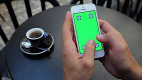 Green screen for typing text vertically with both. A man sits at a table in a cafe with a phone in white, green screen, vertical screen position. Actions: text stock video footage