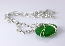Green Sea Glass Necklace. Green weathered glass found on the beaches of the Atlantic.  Nice photo against white background with reflection shows off the jewelry Royalty Free Stock Images
