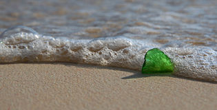 Green Sea Glass on the Shore. A single piece of green sea glass, on the shore as a wave breaks over it Stock Images