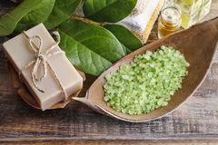 Green sea salt and bar of natural handmade soap on wooden table. Spa time Stock Image