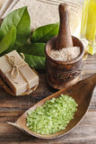 Green sea salt and bar of natural handmade soap on wooden table. Spa time Royalty Free Stock Image