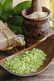 Green sea salt and bar of natural handmade soap on wooden table. Spa time Stock Photo