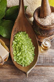 Green sea salt and bar of natural handmade soap on wooden table. Spa time Stock Photos