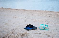 Male and female sneakers slippers on the seashore water blue sky summer. Green sea wave mint sneakers of rubber with bows and rhinestones female and black with Royalty Free Stock Images