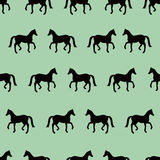 Green seamless pattern with black horses silhouettes Stock Photo
