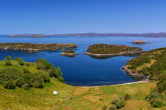 Green seashore with small rocky islands and mountain range in the distance Stock Photo