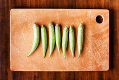 Green seed pods okra on a wooden board. Healthy popular food. Top view of fresh green seed pods okra on a wooden board on a table. Healthy eco food rich in Stock Photography
