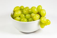 Green seedless grapes in a deep white bowl on a white tale waiting to be eaten royalty free stock image