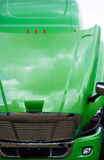Green semi truck cab with open hood and clouds reflection Royalty Free Stock Photo