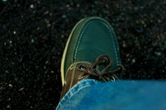 The green and shabby moccasins with a leather lace. The green and shabby moccasins with a lace Royalty Free Stock Photography