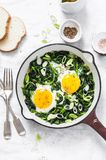 Green shakshuka. Fried eggs with fresh spinach, ramson, leek in a cast iron skillet on a white background. Top view Royalty Free Stock Photography