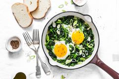 Green shakshuka. Fried eggs with fresh spinach, ramson, leek in a cast iron skillet on a white background. Top view Stock Photography