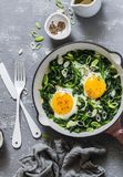 Green shakshuka. Fried eggs with fresh spinach, ramson, leek in a pan on a gray background. Top view Royalty Free Stock Photography