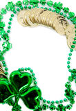 A green shamrock with beads and gold coins as a border on a white background with copy space Stock Images