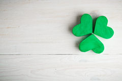Green shamrock clovers on white wooden background Stock Photos