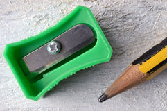 A green sharpener and a pencil on a white table. Stock Images