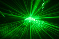 Green shining disco ball in motion. Ligthened by a green laser Royalty Free Stock Photography