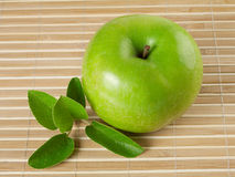 Green shiny apple with a leaf Stock Photos