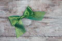 Green shiny bow on light wooden background Royalty Free Stock Photography