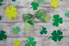 Green shiny bow and shamrocks on light wooden table. Patricks Day Stock Image