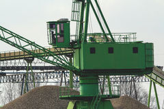 Green ship crane. In a river harbor in Holland loading san form a rivership stock image