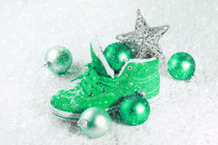 Green shoe with Christmas decorations in the snow. Royalty Free Stock Photography