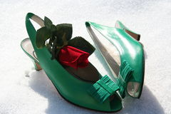 Green shoes with red rose. Woman shoes standing on snow  and is decorated with a red rose Stock Image