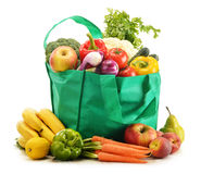 Green shopping bag with grocery products on white Stock Image
