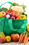 Green shopping bag with grocery products on white Royalty Free Stock Photography