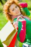 Green shopping begins here. Beautiful girl with shopping bags at summer park Stock Photos