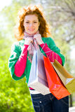Green shopping begins here. Beautiful girl with shopping bags at summer park Stock Images