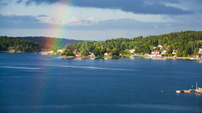 Green shore of Baltic Sea with village and rainbow Stock Images