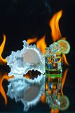 Green shot glass full of ice with lime slices, and white seashel. L and burning fire flames on a black background. Conceptual, commercial and advertising photo stock photography