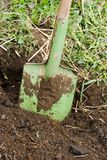 Green shovel. Green metallic shovel in the black ground Royalty Free Stock Photography