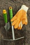 green shovel and rake, garden gloves for seedlings Royalty Free Stock Photos