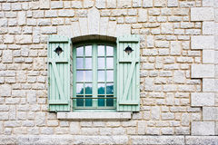 Green shutter window on stone wall Royalty Free Stock Photos